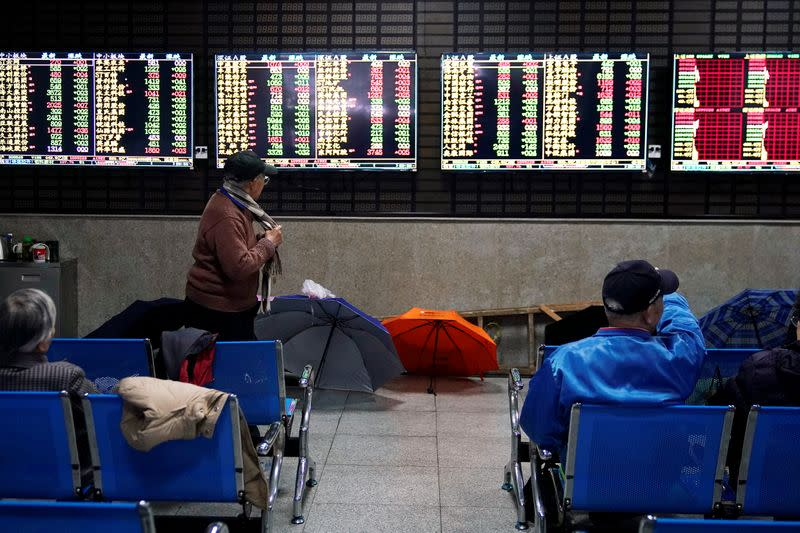 FILE PHOTO: Investors look at screens showing stock information at a brokerage house in Shanghai