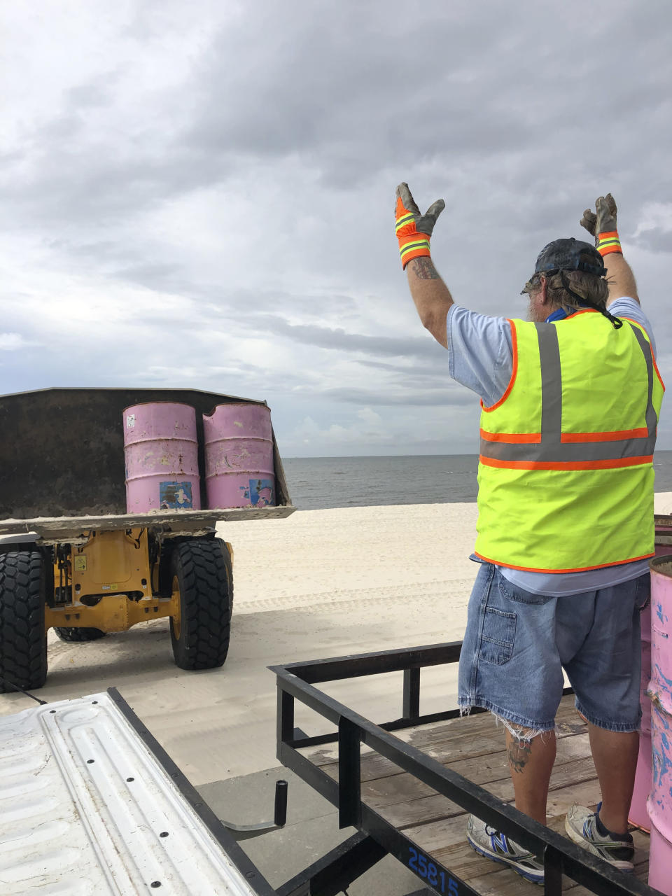 In a photo provided by the Harrison County Board of Supervisors, Harrison County Sand Beach crews remove trash cans from the Harrison County Sand Beach in Gulfport, Miss., Sunday, Aug. 23, 2020, in preparation for Hurricane Marco. (Pat Sullivan via Harrison County Board of Supervisors via AP)