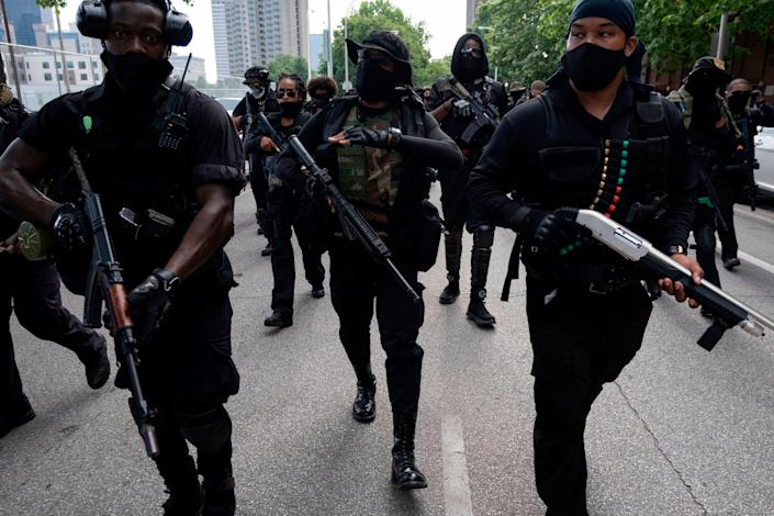 """EDITORS NOTE: Graphic content / John """"Grandmaster Jay"""" Johnson (C) marches with members of the """"Not Fucking Around Coalition"""" (NFAC), an all-Black militia, during a rally to protest the killing of Breonna Taylor, in Louisville, Kentucky on July 25, 2020. (Photo by Jeff Dean / AFP) (Photo by JEFF DEAN/AFP via Getty Images)"""