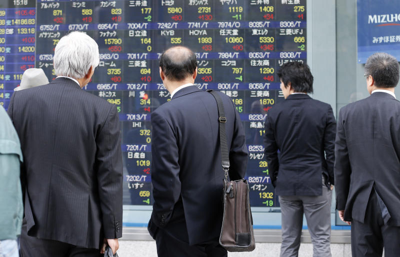 People watch an electronic stock board of a securities firm in Tokyo, Wednesday, April 8, 2013. Japan's Nikkei 225 index rose 105.45 points to 14,285.69 Wednesday as Asian stock markets were powered higher by an improvement in China's trade and yet another record-busting session on Wall Street. (AP Photo/Koji Sasahara)