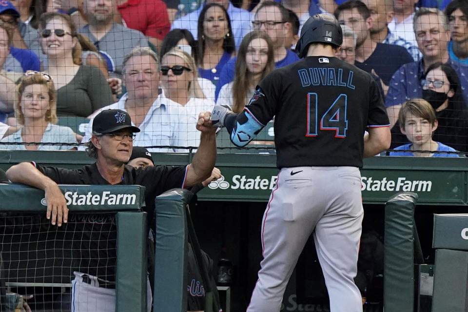 Miami Marlins manager Don Mattingly, left, congratulates Adam Duvall after his grand slam during the third inning of the team's baseball game against the Chicago Cubs in Chicago, Friday, June 18, 2021. (AP Photo/Nam Y. Huh)