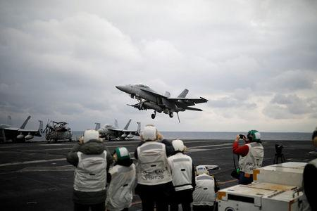 "FILE PHOTO - A U.S. F18 fighter jet lands on the deck of U.S. aircraft carrier USS Carl Vinson during an annual joint military exercise called ""Foal Eagle"" between South Korea and U.S., in the East Sea, South Korea, March 14, 2017.  REUTERS/Kim Hong-Ji/File Photo"