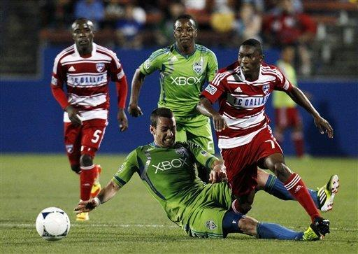 Seattle Sounders' Zach Scott takes down FC Dallas' Fabian Castillo (7) as Castillo tried to advance the ball in the second half of an MLS soccer match, Wednesday, May 9, 2012, in Frisco, Texas. Scott was issued a yellow card for the offense in the Sounders' 2-0 win. (AP Photo/Tony Gutierrez