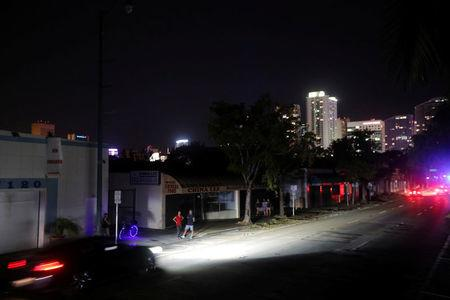 Local residents stand in the darkness as many areas of Miami still without electricity after Hurricane Irma strikes Florida, in Little Havana, Miami, Florida, September 11, 2017. REUTERS/Carlos Barria