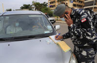 A Lebanese policeman writes a ticket for a car that violated the odd or even number plates car bans, as the country began a two-week lockdown to limit the spread of coronavirus that killed dozens of people over the past days, in Beirut, Lebanon, Saturday, Nov. 14, 2020. The lockdown comes after the number cases increased sharply in recent weeks around Lebanon straining the country's medical sector where intensive care units are almost full. (AP Photo/Hussein Malla)
