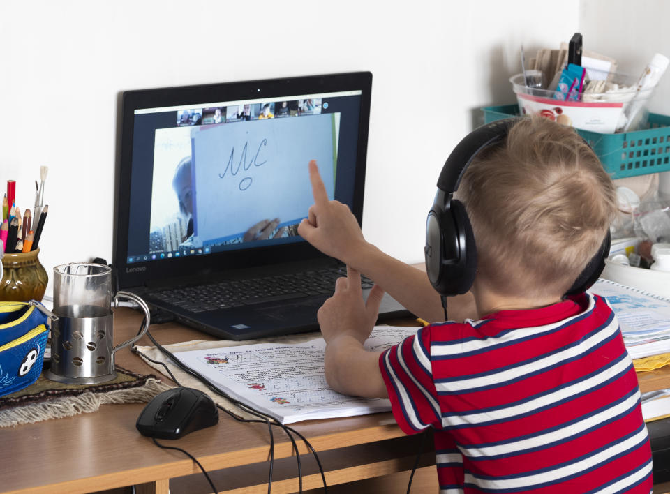 elementary student wearing red and white striped t-shirt pointing to laptop while learning at home