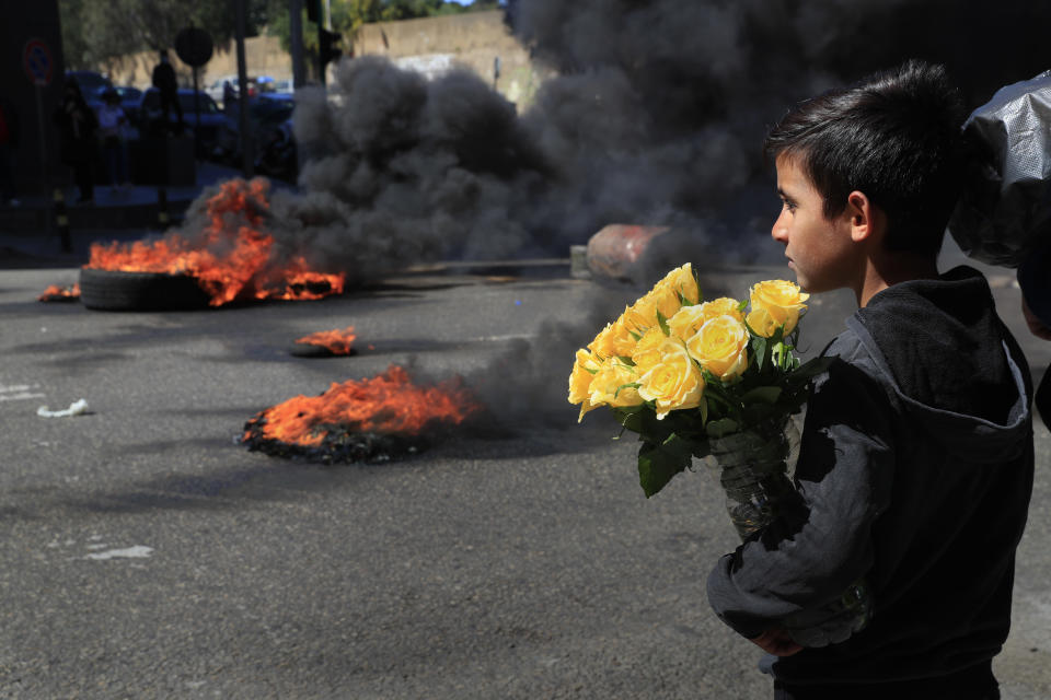 A Syrian boy who sells flowers on the street watches protesters burn tires to block a main road during a protest against the increase in prices of consumer goods and the crash of the local currency, in Beirut, Lebanon, Tuesday, March 16, 2021. Scattered protests broke out on Tuesday in different parts of the country after the Lebanese pound hit a new record low against the dollar on the black market. (AP Photo/Hussein Malla)