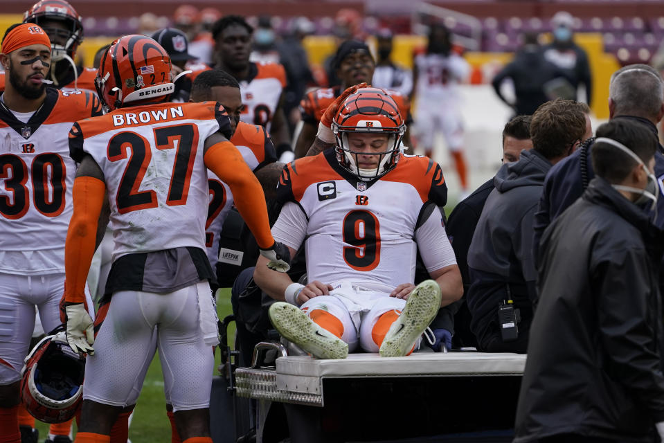 Joe Burrow (9) is consoled by teammates as he is carted off the field during the second half of an NFL football game against the Washington Football Team, Sunday, Nov. 22, 2020, in Landover. Burrow was carted off the field with a left knee injury. (AP Photo/Susan Walsh)