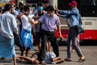 Military supporter points a sharp object as he confronts anti-coup protesters during a military support rally in Yangon