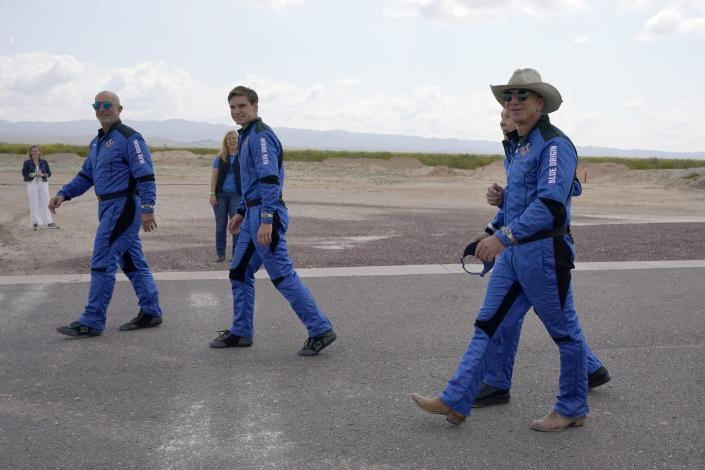 Mark Bezos, from left, Oliver Daemen, Wally Funk, right rear, and Jeff Bezos, founder of Amazon and space tourism company Blue Origin walk out to see the nearby rocket that landed safely after their launch from the spaceport near Van Horn, Texas, Tuesday, July 20, 2021. (AP Photo/Tony Gutierrez)