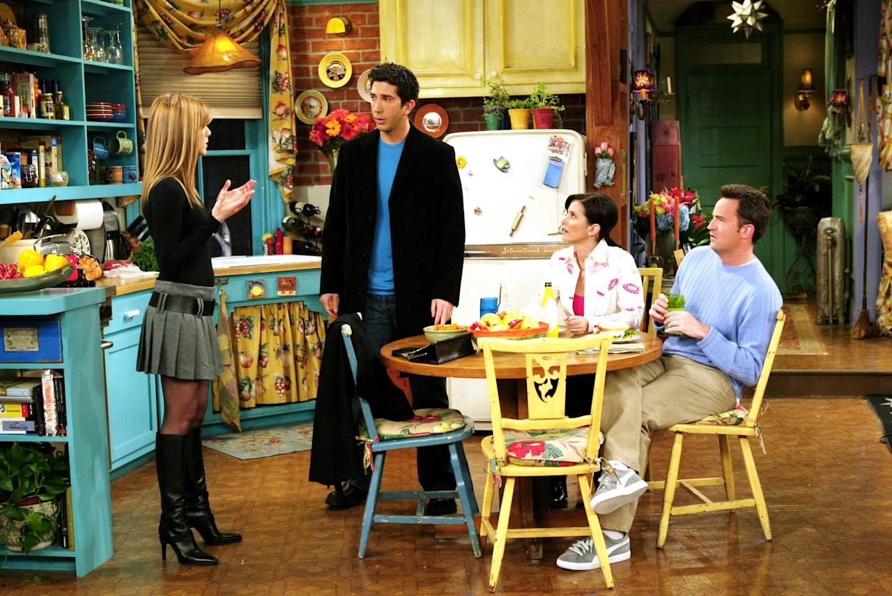 <p>Rachel Green wears a black fitted jumper with a gray miniskirt and black knee-high boots.</p>