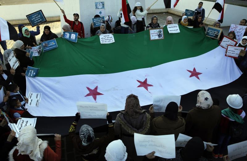 Syrians hold placards and a giant Syrian revolutionary flag as they chant slogans against the Syrian  government during a sit-in marking the eighth anniversary of the Syrian civil war, in Martyrs' Square in downtown Beirut, Lebanon, Sunday, March 17, 2019. (AP Photo/Bilal Hussein)