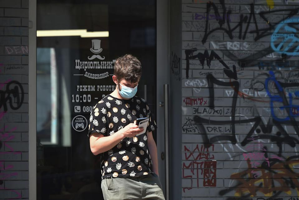 A man wearing a protective face mask, queue outside a barber shop which reopened on May 11, 2020, in Kiev, after months-long closures aimed at stemming the spread of the COVID-19 outbreak, the novel coronavirus. - From May 11 2020 Ukrainians will be allowed to visit outdoor cafes, beauty salons, dental clinics, parks and squares as Ukraine partially lifts some restrictions imposed to curb the spread of the novel coronavirus. (Photo by Sergei SUPINSKY / AFP) (Photo by SERGEI SUPINSKY/AFP via Getty Images)