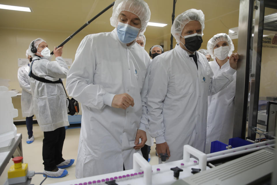 French President Emmanuel Macron, second right, and plant manager Wladimir Guitel, visit the Delpharm plant in Saint-Remy-sur-Avre, west of Paris, Friday, April 9, 2021 in Paris. The Delpharm plant started bottling Pfizer vaccines this week as France tries to make its mark on global vaccine production, and speed up vaccinations of French people amid a new virus surge. (AP Photo/Christophe Ena, Pool)