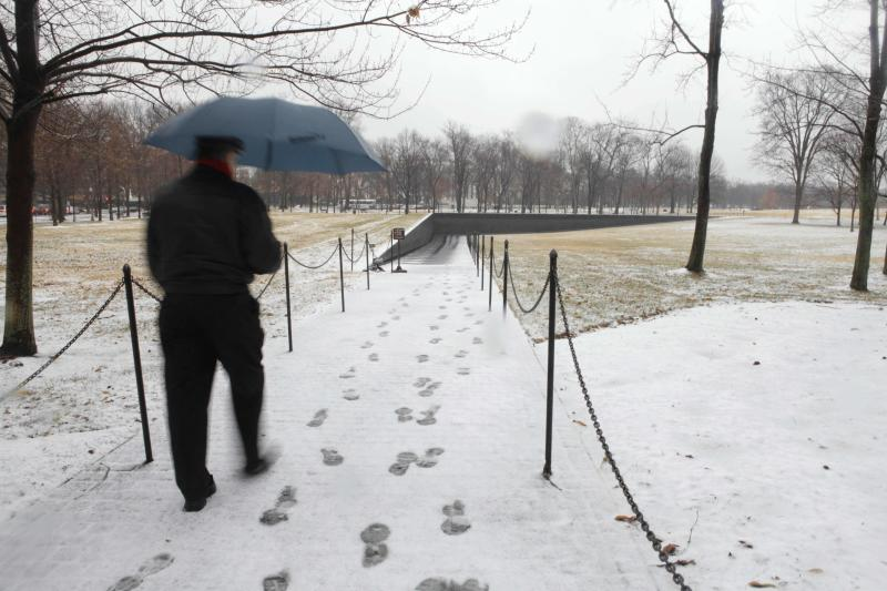 A man walks through slushy snow in the rain while visiting the Vietnam Veterans Memorial in Washington, Wednesday, Jan. 26, 2011. Snow mixed with rain in the early morning, while more snow is forecast for tonight according to the National Weather Service. (AP Photo/Jacquelyn Martin)