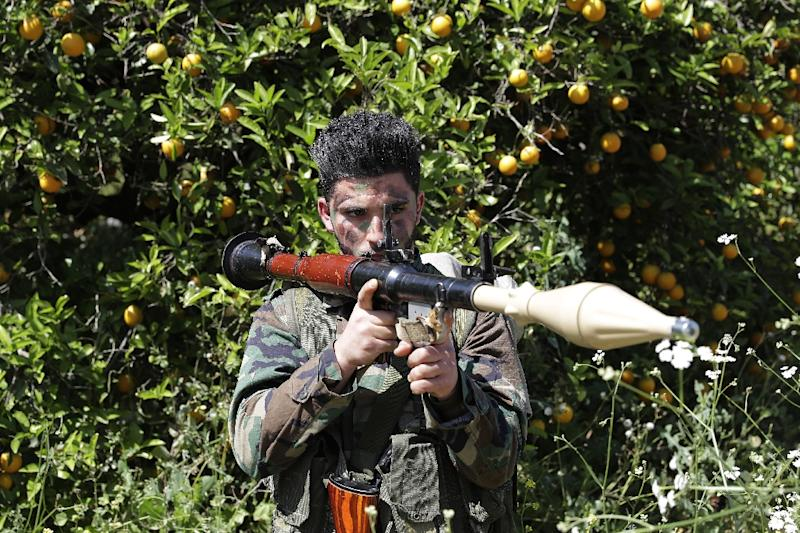 A Hezbollah fighter stands at attention in an orange field near the town of Naqura on the Lebanese-Israeli border on April 20, 2017 (AFP Photo/JOSEPH EID)