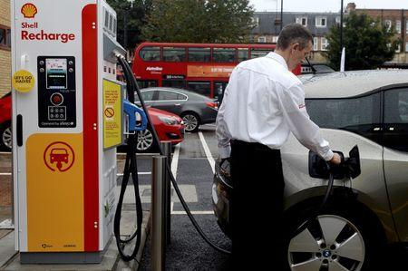 A member of staff charges an electric car at the Holloway Road Shell station where Shell is launching its first fast electric vehicle charging station in London