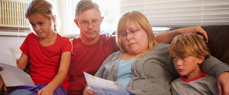 Unhappy family sitting on sofa and looking at bills