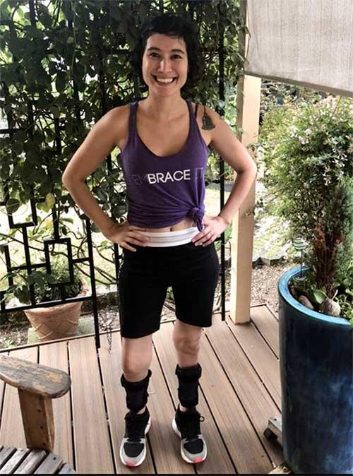 Julie wearing her EmBRACE It t-shirt and a pair of black AFOs.