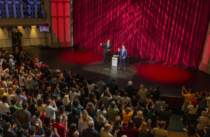 University of Southern California students stand up for Democratic presidential candidate and former South Bend Mayor Pete Buttigieg, right, and moderator Fox 11 anchor, Elex Michaelson, left, during the USC Dornsife Center for the Political Future town hall in Los Angeles Thursday, Feb. 20, 2020. (AP Photo/Damian Dovarganes)