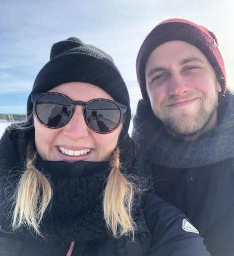 A selfie photo of Luke Bevan and Tova Ronnersjö both rugged up in warm clothes with snow visible in the background.