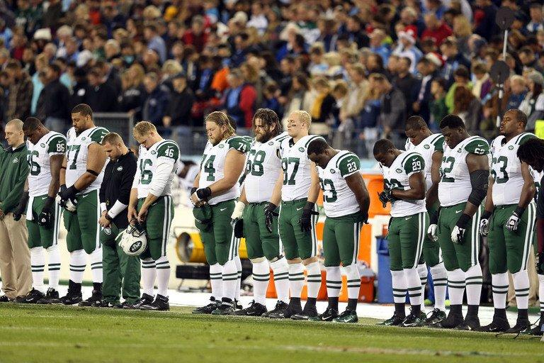 The New York Jets stand on the sideline in a moment of silence on December 17, 2012 for the victims of the mass shooting