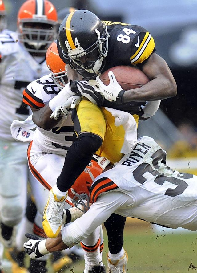 Pittsburgh Steelers wide receiver Antonio Brown (84) tries to break through a tackle by Cleveland Browns defensive back Julian Posey (38) in the third quarter of an NFL football game on Sunday, Dec. 29, 2013, in Pittsburgh. The Steelers won 20-7. (AP Photo/Don Wright)
