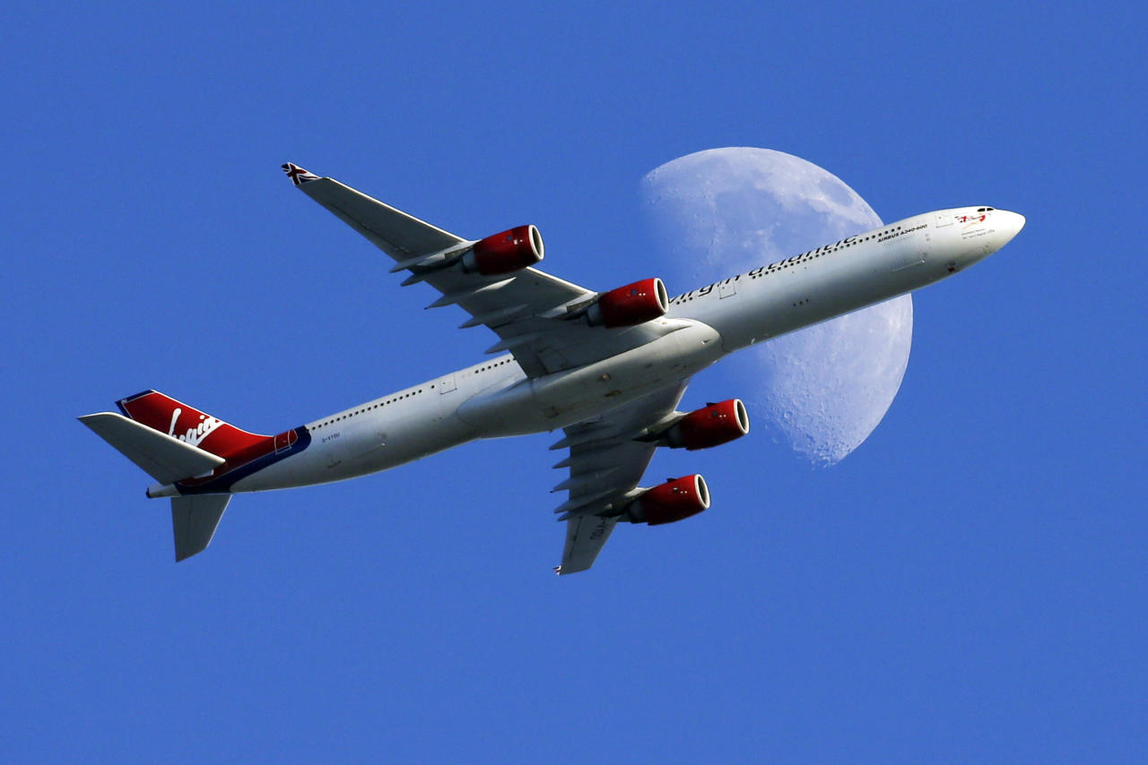 FILE - In this Sunday, Aug. 23, 2015, file photo, a Virgin Atlantic passenger plane crosses a waxing gibbous moon on its way to the Los Angeles International Airport, in Whittier, Calif. On Tuesday, Dec. 6, 2016, Alaska Airlines said it has won government approval to buy rival Virgin America after agreeing to reduce its flight-selling partnership with American Airlines. (AP Photo/Nick Ut, File)