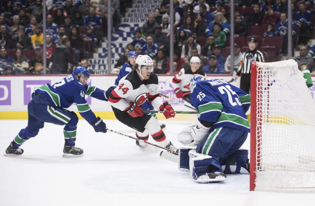 New Jersey Devils' Miles Wood (44) puts a shot over the crossbar behind Vancouver Canucks goalie Jacob Markstrom, of Sweden, as Quinn Hughes (43) defends during the first period of an NHL hockey game in Vancouver, British Columbia, Sunday, Nov. 10, 2019. (Darryl Dyck/The Canadian Press via AP)