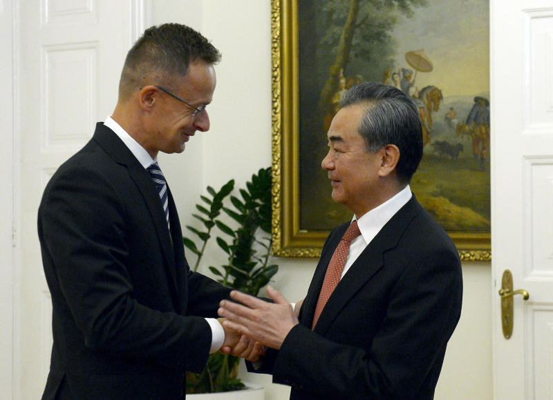 Chinese Foreign Minister Wang Yi, right, shakes hands with Hungarian Minister of Foreign Affairs and Trade Peter Szijjarto during their meeting in the latter's office in Budapest, Hungary, Friday, July 12, 2019. (Lajos Soos/MTI via AP)