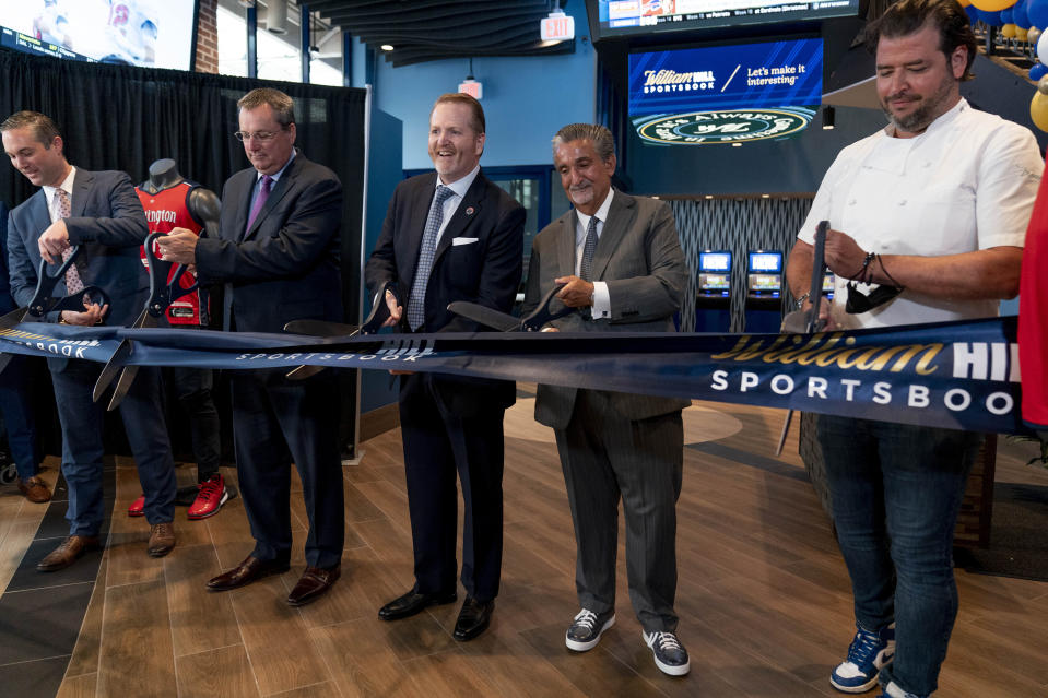 From left, Caesars Sports & Online Gaming Co-President Eric Hession, CEO of Caesars Entertainment CEO Tom Reeg, Monumental Sports & Entertainment Business Operations & Chief Commercial Officer President Jim Van Stone, Founder & CEO of Monumental Sports & Entertainment and owner of the Washington Wizards and the Washington Capitals Ted Leonsis, and chef Nicholas Stefanelli participate in a ribbon cutting for the William Hill Sportsbook at Monumental Sports & Entertainment's Capital One Arena in Washington, Wednesday, May 26, 2021. The William Hill Sportsbook is the first ever sports betting venue to open within a U.S. professional sports facility. (AP Photo/Andrew Harnik)