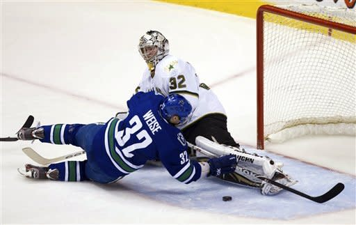 Vancouver Canucks' Dale Weise, left, falls to the ice in front of Dallas Stars goalie Kari Lehtonen, of Finland, after being tripped by Adam Pardy, not pictured, during the second period of an NHL hockey game, Friday, March 30, 2012, in Vancouver, British Columbia. (AP Photo/The Canadian Press, Darryl Dyck)