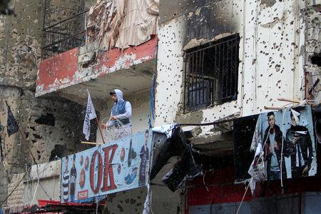A man stands on a bullet-riddled building inside the Ain el-Hilweh refugee camp near Sidon