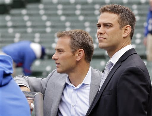 Chicago Cubs President of Baseball Operations Theo Epstein, right, and general manager Jed Hoyer watch the team's batting practice before a baseball game against the Milwaukee Brewers in Chicago, Monday, April 8, 2013. (AP Photo/Nam Y. Huh)
