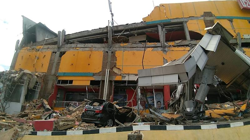 A collapsed building in Palu: an air traffic controller is being hailed as a hero after staying at his post during the quake