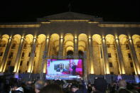 Supporters of Georgian ex-President Mikheil Saakashvili's United National Movement watch his address on a big screen in front of the Parliament's building after the parliamentary elections in Tbilisi, Georgia, Saturday, Oct. 31, 2020. The Georgian Dream party, created by billionaire Bidzina Ivanishvili has claimed victory in the election hotly contested by an alliance formed around the country's ex-President Mikheil Saakashvili, who is in self-imposed exile in Ukraine. (AP Photo/Zurab Tsertsvadze)