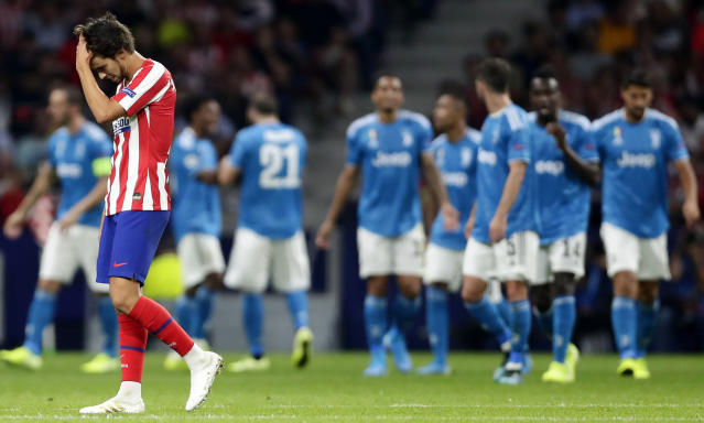 Atletico Madrid's Joao Felix reacts as Juventus' Juan Cuadrado celebrates with teammates scoring the opening goal during the Champions League Group D soccer match between Atletico Madrid and Juventus at Wanda Metropolitano stadium in Madrid, Spain, Wednesday, Sept. 18, 2019. (AP Photo/Manu Fernandez)