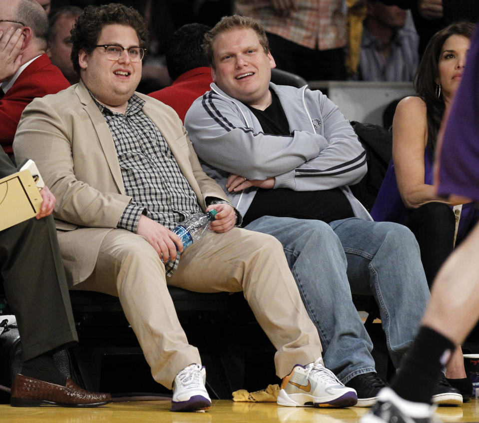 Jonah Hill, left, and a friend watch the Los Angeles Lakers play the Phoenix Suns during the first half of Game 5 of the NBA basketball Western Conference finals Thursday, May 27, 2010, in Los Angeles. (AP Photo/Chris Carlson)