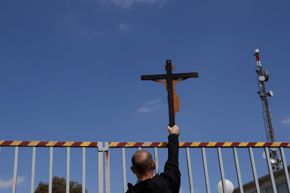 """A protestor holds a cross, outside Cyprus' national broadcasting building, during a protest, in capital Nicosia, Cyprus, Saturday, March 6, 2021. The Orthodox Church of Cyprus is calling for the withdrawal of the country's controversial entry into this year's Eurovision song context titled """"El Diablo"""", charging that the song makes an international mockery of country's moral foundations by advocating """"our surrender to the devil and promoting his worship."""" (AP Photo/Petros Karadjias)"""
