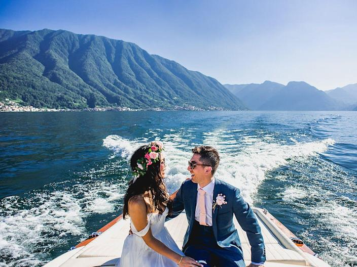 A bride and groom laugh on a boat on Lake Como.