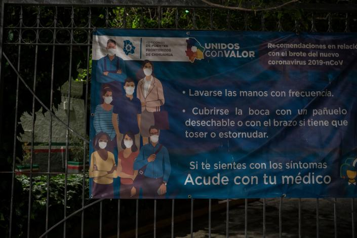 """A poster with information about COVID-19 is pictured on April 1, 2020 at the Paso del Norte International Bridge in Ciudad Jua?rez in the state of Chihuahua, Mexico. - As immigration courts have been closed due to the coronavirus, COVID-19, pandemic people seeking asylum in Migrant Protection Protocols program, better known as the """"Remain in Mexico"""" policy, are still expected to show up in the dangerous city centre before dawn to receive new dates despite stay-at-home order on both sides of the border. (Photo by Paul Ratje / Agence France-Presse / AFP) (Photo by PAUL RATJE/Agence France-Presse/AFP via Getty Images)"""