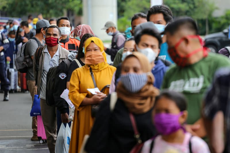 FILE PHOTO: Passengers wearing protective face masks line up to rapid antigen test