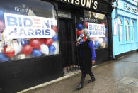 A woman wearing a face mask walks past a pub supporting Joe Biden and Kamala Harris in Ballina, Ireland, Wednesday, Jan. 20, 2021. Joe Biden's great-great grandfather Patrick Blewitt was born in Ballina, County Mayo, in 1832. He left for the US in 1850, aged 18. (AP Photo/Peter Morrison)