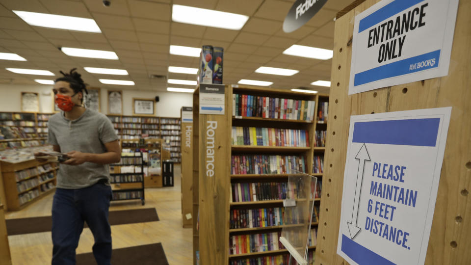 Signs are posted for social distancing as Dan Loftus organizes books at Half Price Books, Monday, May 11, 2020, in Mayfield Heights, Ohio. (AP Photo/Tony Dejak)