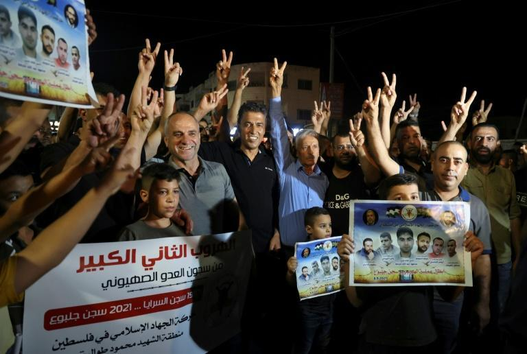 """Palestinians in the Jenin camp in the West Bank flash """"V"""" for victory signs over the escape (AFP/JAAFAR ASHTIYEH)"""