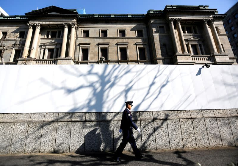 FILE PHOTO: A security guard walks past in front of the Bank of Japan headquarters in Tokyo