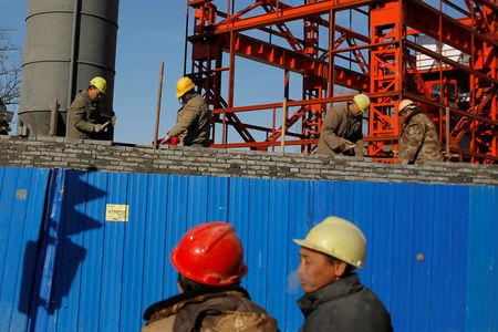 FILE PHOTO: Workers lay bricks to build a wall around a construction site in Beijing, China, December 15, 2017.  REUTERS/Thomas Peter/File Photo