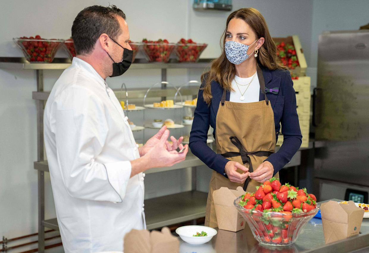 Britain's Catherine, Duchess of Cambridge, Patron of the All England Lawn Tennis Club, talks with with chef Adam Fargin as she prepares strawberries in the Wingfield kitchen during her visit on the fifth day of the 2021 Wimbledon Championships at The All England Tennis Club in Wimbledon, southwest London, on July 2, 2021. - RESTRICTED TO EDITORIAL USE (Photo by AELTC/Thomas Lovelock / POOL / AFP) / RESTRICTED TO EDITORIAL USE (Photo by AELTC/THOMAS LOVELOCK/POOL/AFP via Getty Images)