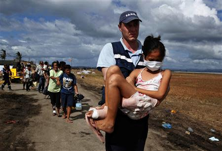 A volunteer from a French rescue team carries an injured girl to a military plane during an evacuation at Tacloban airport in the Typhoon Haiyan devastated city of Tacloban November 16, 2013. Survivors began rebuilding homes destroyed by Haiyan, one of the world's most powerful typhoons, and emergency supplies flowed into ravaged Philippine islands, as the United Nations more than doubled its estimate of people made homeless to nearly two million. REUTERS/Bobby Yip