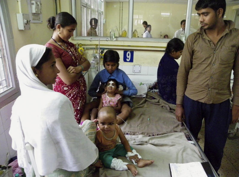 In this Tuesday, April 2, 2013 photo, an Indian child in a pink shirt with a white bandage on her face undergoes treatment for encephalitis at a hospital in Gorakhpur in Uttar Pradesh state, India. Encephalitis is sweeping through northern India, killing at least 118 children in what officials worry could become the deadliest outbreak in nearly a decade. While India's efforts against polio and tuberculosis get plenty of attention, the poor farmers and day laborers of eastern Uttar Pradesh state face an almost-silent health emergency, battling a disease that has killed thousands of children over the past eight years. (AP Photo/Biswajeet Banerjee)